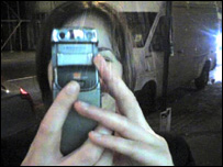Woman taking picture with camera phone, BBC