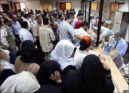 Palestinians queue at a bank in Gaza City
