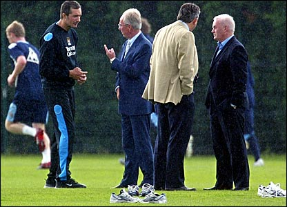 Sven-Goran Eriksson chats with coaches at a wet Manchester City training ground