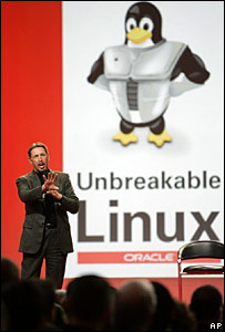 Larry Ellison of Oracle stands in front of a linux poster