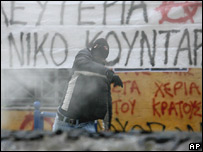 A demonstrator throws a gasoline bomb at riot police during a student march in central Athens