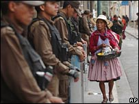 A woman walks past riot police guarding the state government building in Cochabamba