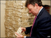 Colombia's Defence Minister Juan Manuel Santos counting dollars seized during a police operation in Cali, Colombia