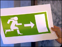 Emergency exit sign showing woman running