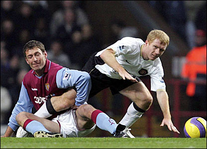 Chris Sutton (left) battles for the ball with Manchester United's Paul Scholes - the game would be Sutton's last