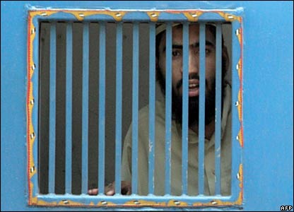 A man looks from within a police van after surrendering near the Red Mosque