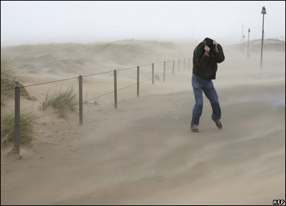 A man struggles through a sand storm on a beach at Egmond Aan Zee in the Netherlands