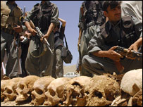Soldiers pose near the skulls discovered near Kabul, Afghanistan  (photo: Massoud Hossaini)