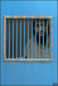 A Pakistani radical Islamist student in a police van after surrendering outside the Red Mosque