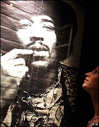 Woman looking at Jimi Hendrix poster
