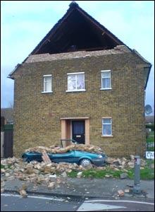 Bricks blown from a house crushing a car