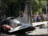 People stand behind a security cordon after a cargo plane crashed in Mexico