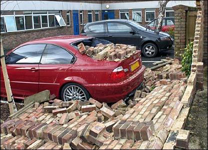 Car damaged by fallen wall