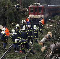 Fallen trees are removed from in front of a train which was stranded overnight near Ceske Velenice, Czech Republic