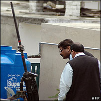 Security officials examine an anti-aircraft gun on the roof of the house