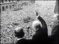 Churchill on a balcony raising the victory salute