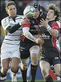 Gavin Henson (left) gets to grips with Sale's Magnus Lund and Ben Foden