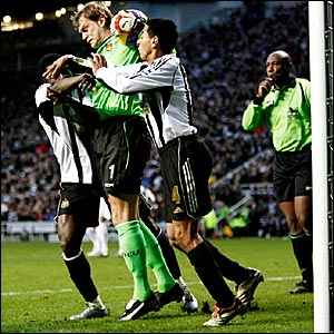 Newcastle players Obafemi Martins (left) and Nolberto Solano (right) try to get the ball off West Ham keeper Roy Carroll