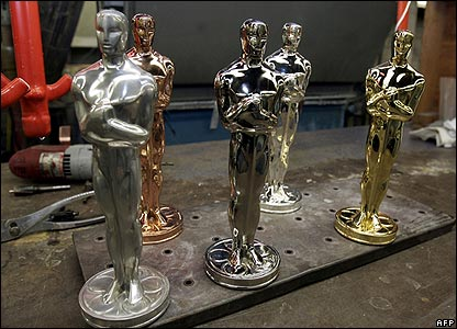 Five Oscars at different stages of manufacture