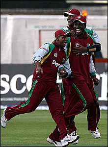 Chris Gayle (centre) is congratulated after taking the catch to remove Dimitri Mascarenhas