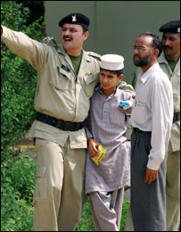 جندي من القوات شبه العسكرية يصيح مشيرا بيده بينما إلى جانبه أحد الأطفال الذين تمكنوا من الخروج من المدرسة الإسلامية للمسجد الأحمر، 7 يوليو/تموز 2007 - الصورة من أسوشييتدبرس