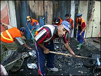عراقيون ينظفون المنطقة التي وقع فيها الانفجار في العاصمة بغداد