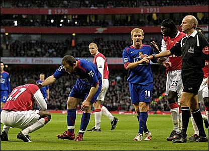 Arsenal's Emmanuel Eboue (left) is tended to by Manchester United's Wayne Rooney