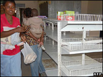Shoppers pass empty supermarket shelves
