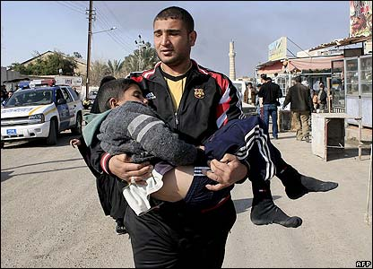 An Iraqi man carries a young boy away from the bombed market place