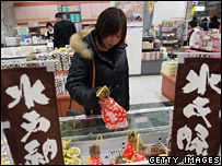 A Japanese women picks a bag of natto from a supermarket freezer