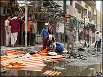 Men clean up debris from the site of a car bomb attack in east Baghdad (9 July)