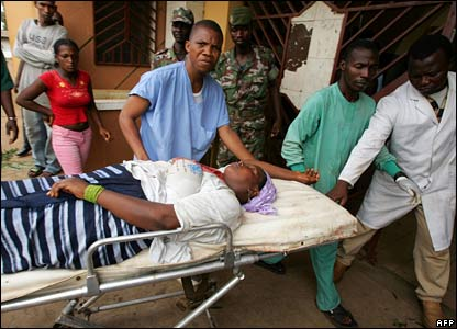 Emergency workers carry an injured woman on a stretcher to a hospital in Conakry