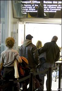 People queue up outside a passport office in downtown Ottawa, Canada