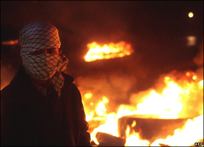 A Lebanese supporter of the Hezbollah-led opposition parties stands near burning tyres in Beirut