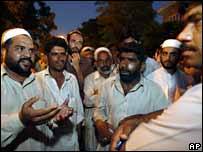Men wait for news of family members inside the Red Mosque
