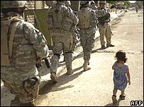 An Iraqi child walking alongside US troops in Baghdad