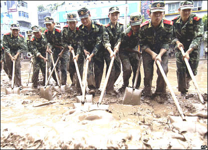 Soldiers of the People's Armed Police Force clean silt in the flooded old city area of Guangan.