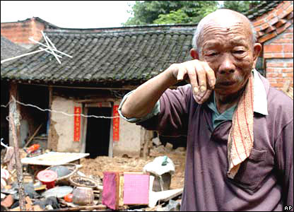 An old man weeps over the destruction caused by flooding to his home in China