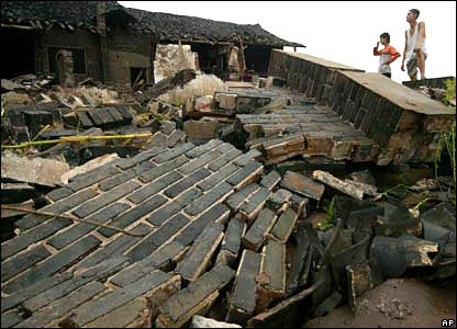 Local residents look at collapsed houses after floods in Guangan.