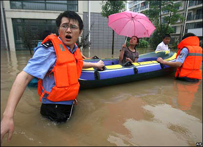 A woman in a dinghy is evacuated by rescuers.