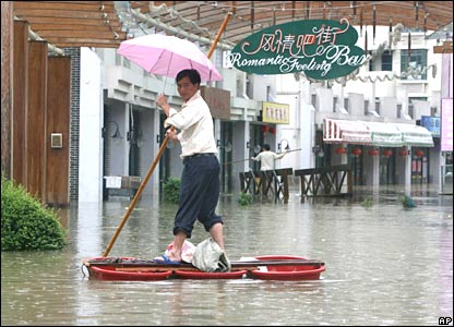 A resident makes his way on a raft made from plastic basins in flood waters after torrential rain hit Nanjing China.