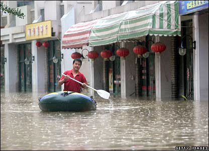 A man rows a rubber dingy on a street submerged by flood waters in the city of Nanjing of Jiangsu province.