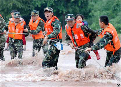 Firemen rescue passengers from a coach that was trapped in water in Guangan.