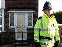 A police officer outside a house in Cheetham Hill, Manchester