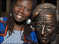 Monica Arac de Nyeko poses next to a statue of Michael Caine, the founder of the award (Picture from Raitt Orr & Associates)