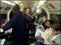 Commuters reading free papers on the Tube