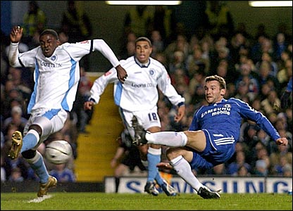 Andriy Shevchenko (right) has a shot blocked by Wycombe's Will Antwi (left)