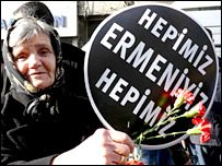 Old woman carried flowers and a placard