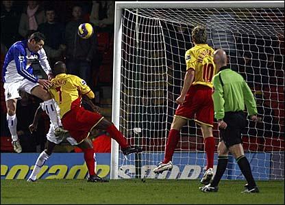 Blackburn's Brett Emerton (left) heads into his own net