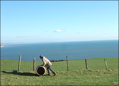 A lone man rolls a barrell up from Branscombe Beach. Photo by David Fothergill